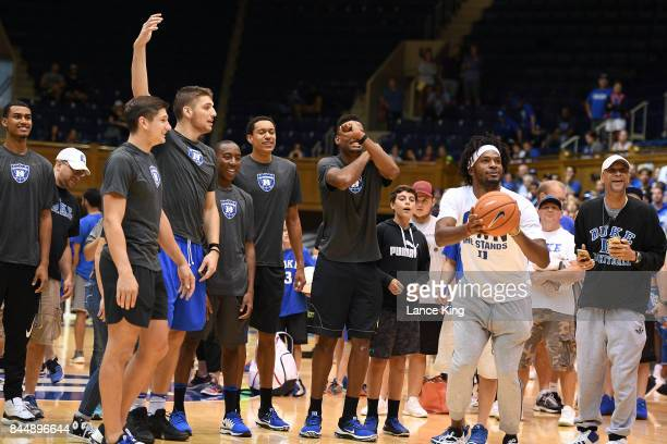 Players and guests of the Duke Blue Devils look on as former Duke basketball player Justise Winslow shoots the ball during the Duke Basketball...