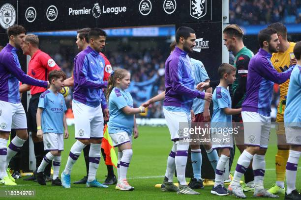 Players and mascots shake hands prior to the Premier League match between Manchester City and Aston Villa at Etihad Stadium on October 26 2019 in...