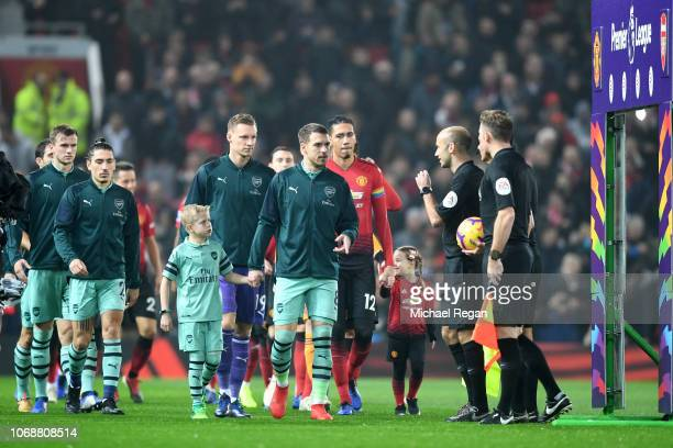 Players and mascots walk out prior to during the Premier League match between Manchester United and Arsenal FC at Old Trafford on December 5 2018 in...