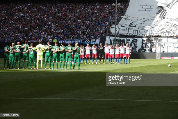 Players and match officials observe a minute's silence in memory of the victims of Thursday's terrorist attacks in Spain before the Bundesliga match...