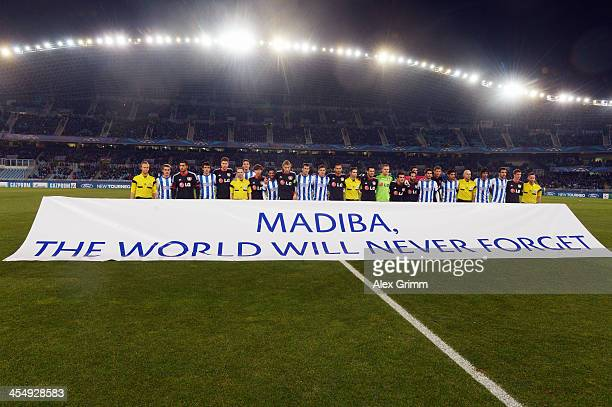 Players and match officials pose behind a banner reading 'Madiba the world will never forget' to honour Nelson Mandela prior to the UEFA Champions...