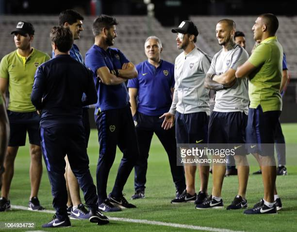 Players and members of Boca Juniors remain on the pitch of the Monumental stadium in Buenos Aires after authorities postponed the allArgentine Copa...