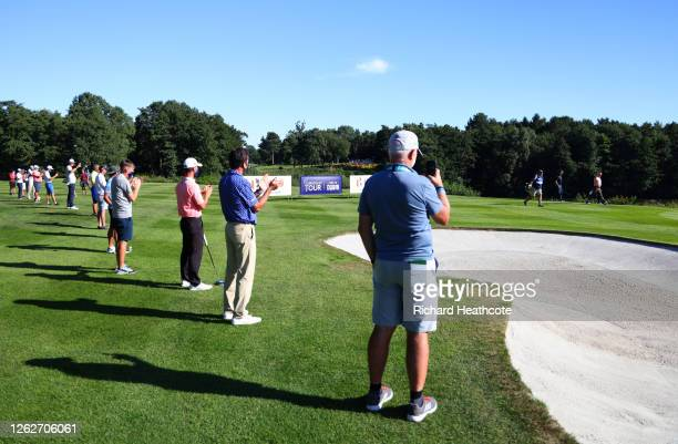 Players and members of staff applaud Miguel Angel Jimenez of Spain off the 18th green as he makes his 707th European tour start, a tour appearance...
