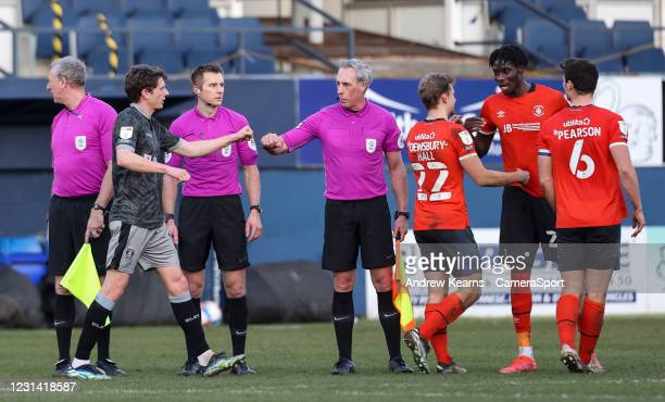 Players and officials bump fists at the end of the match during the Sky Bet Championship match between Luton Town and Sheffield Wednesday at...