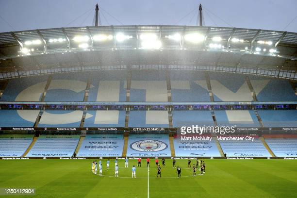 Players and officials line up for a minutes silence during the Premier League match between Manchester City and Arsenal FC at Etihad Stadium on June...