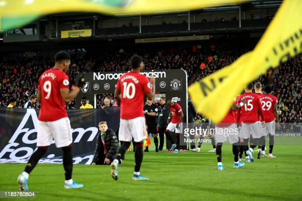 Players and officials make their way out onto the pitch in-front of a No Room for Racism banner prior to the Premier League match between Norwich...