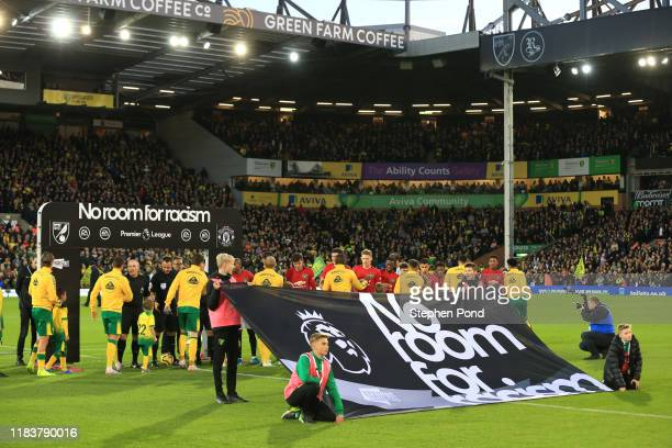 Players and officials make their way out onto the pitch infront of a No Room for Racism banner prior to the Premier League match between Norwich City...