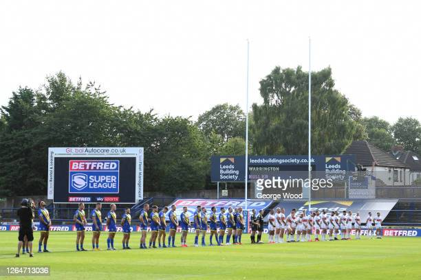 Players and officials observe a minutes silence in memory for those who have lost their lives during the COVID19 Pandemic ahead of the Betfred Super...