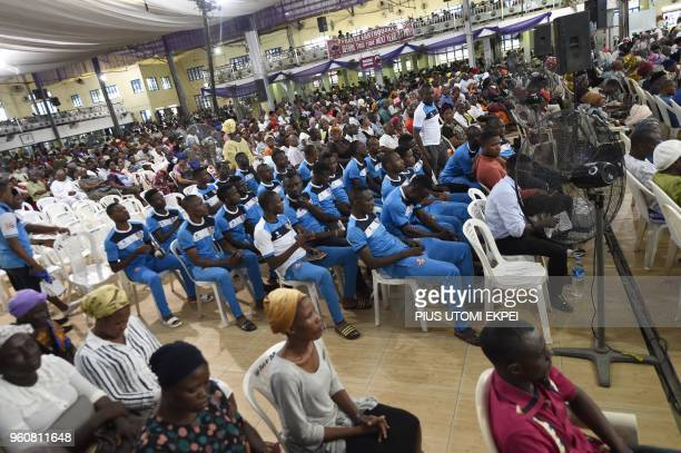 Players and officials of Mountain of Fire and Miracles Ministries football club sit to pray along with other worshippers in the church at the...