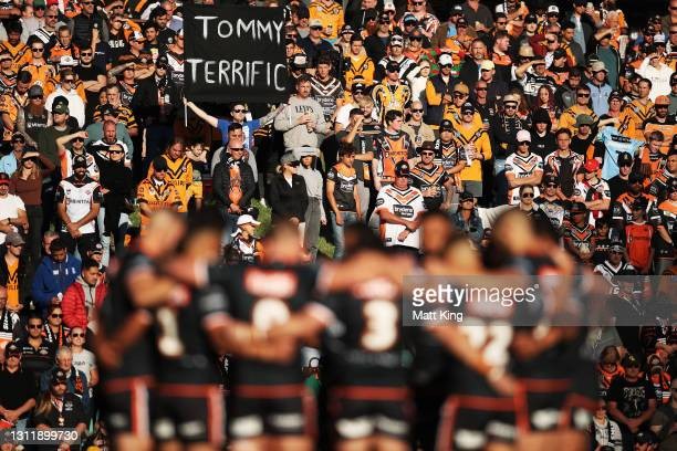 Players and spectators pay respect during a minutes silence for the late Tommy Raudonikis during the round five NRL match between the Wests Tigers...