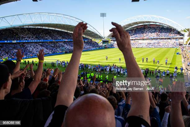 Players and staff of Huddersfield Town celebrate with the fans at full time during the Premier League match between Huddersfield Town and Arsenal at...