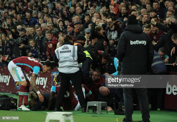 Players and stewards assist fans after a pitchside barrier collapses during the Premier League match between West Ham United and Tottenham Hotspur at...