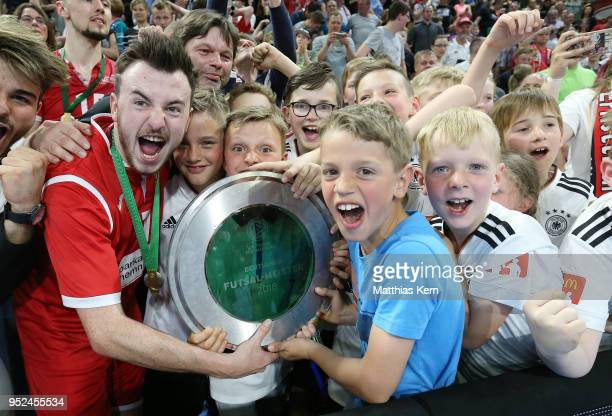 Players and supporters of Hohenstein Ernstthal celebrate with the trophy after winning the German Futsal Championship final match between VfL...