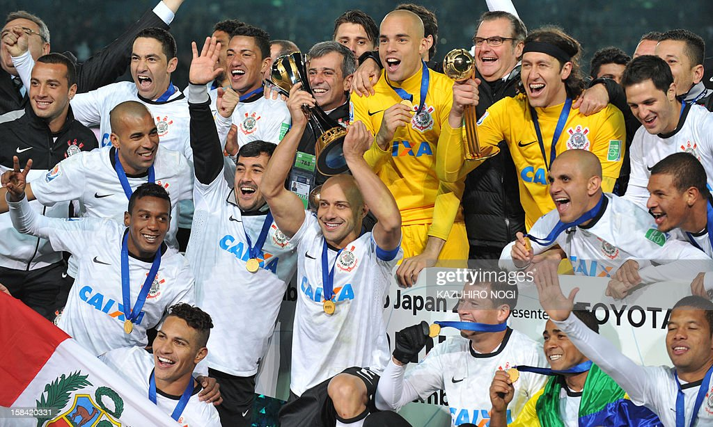 Players and team staff celebrate their victory over English Premier League team Chelsea during the award ceremony of the 2012 Club World Cup football after their final match at Yokohama on December 16, 2012.