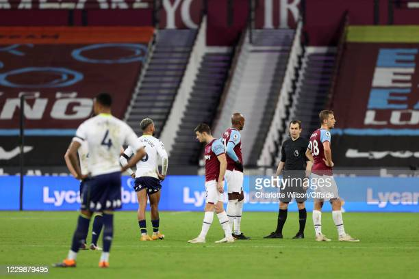 Players and the referee wait for a Video Assistant Referee decision to be made during the Premier League match between West Ham United and Aston...