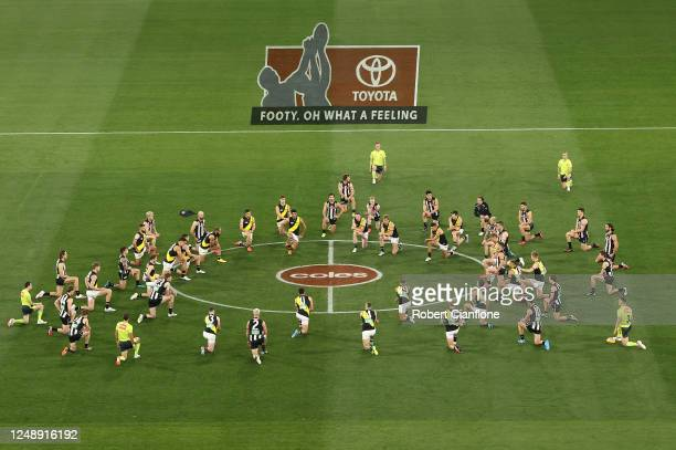 Players and umpires kneel on the centre circle during the round 2 AFL match between the Collingwood Magpies and the Richmond Tigers at Melbourne...