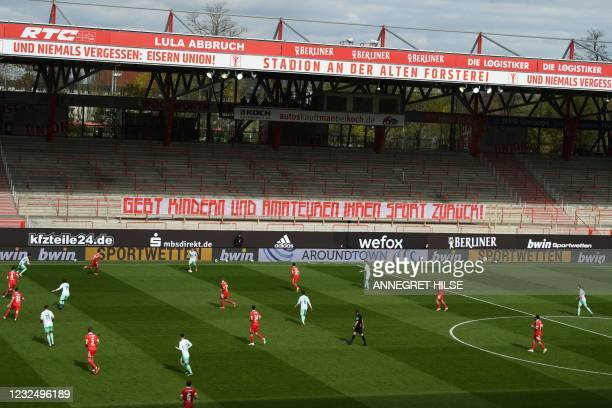 """Players are seen on the pitch as banner on the empty terraces reads """"Give sport back to children and amateurs!"""" during the German first division..."""