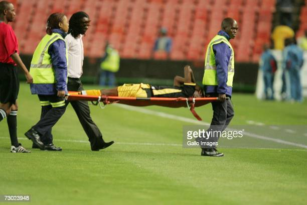 Players are stretchered off after strong winds blow advertising boards onto the pitch during the PSL match between the Orlando Pirates and the Black...