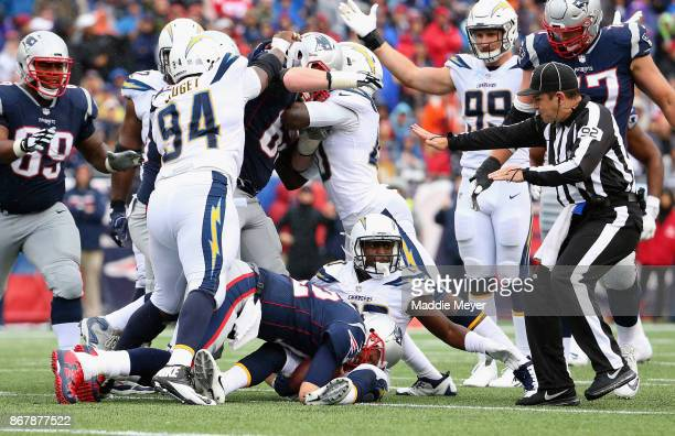 Players argue after Tom Brady of the New England Patriots is tackled by Desmond King of the Los Angeles Chargers during the third quarter of a game...