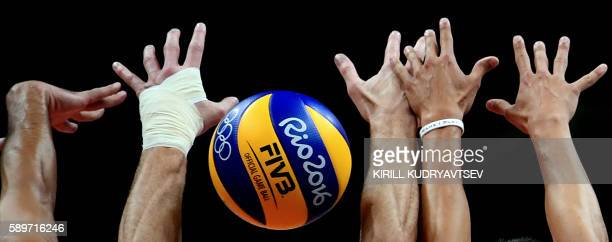 US players attempt to block the ball during the men's qualifying volleyball match between the USA and Mexico at the Maracanazinho stadium in Rio de...