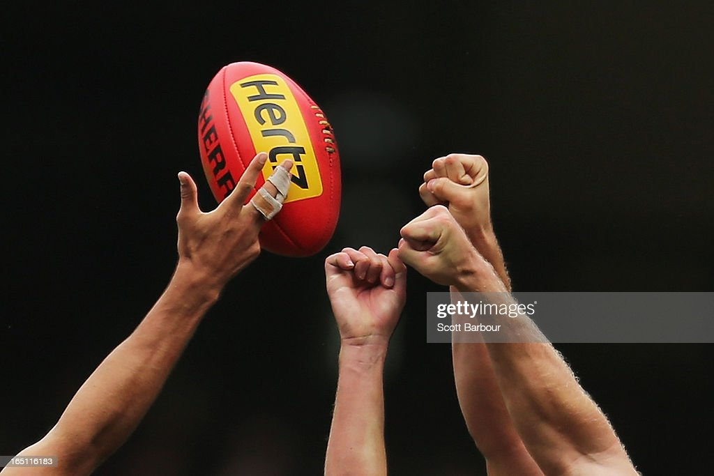 Players attempt to punch the ball as they compete for it during the round one AFL match between the Melbourne Demons and Port Adelaide Power at the Melbourne Cricket Ground on March 31, 2013 in Melbourne, Australia.
