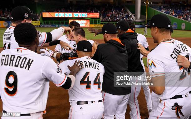 Players celebrate after JT Realmuto of the Miami Marlins hit a walkoff double to score Miguel Rojas during the ninth inning of the game against the...