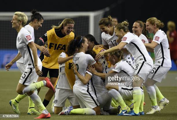 USA players celebrate after winning the semifinal football match between USA and Germany during their 2015 FIFA Women's World Cup at the Olympic...