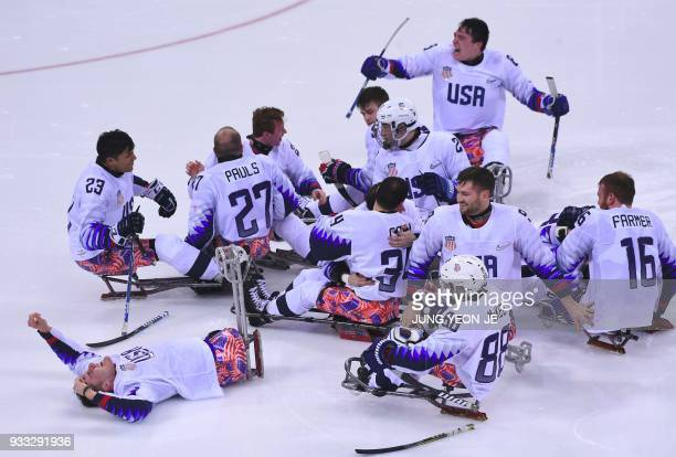 US players celebrate their victory after the ice hockey gold medal game between Canada and the US at the Gangneung Hockey Centre during the...