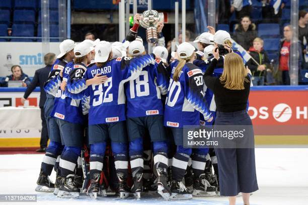 US players celebrate with the trophy during the medal ceremony after their 21 shootout victory in the IIHF Women's Ice Hockey World Championships...