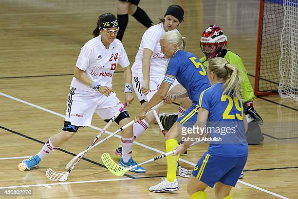 Players challenge for the ball during the World University Championship Floorball match between Switzerland and Sweden at the Sports Hub OCBC Arena...