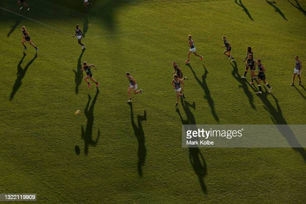 Players chase the down the ball during the round 12 AFL match between the Carlton Blues and the West Coast Eagles at Sydney Cricket Ground on June...