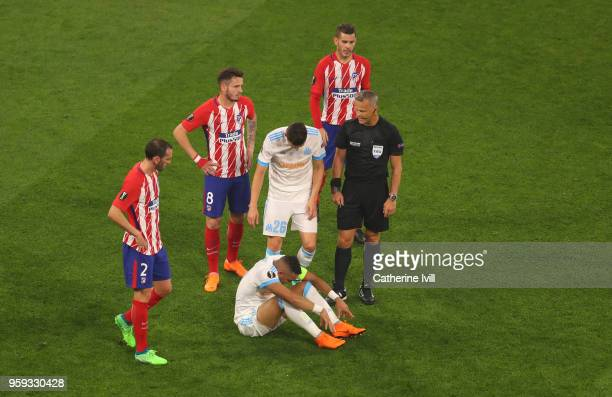 Players check on an injured Dimitri Payet of Marseille during the UEFA Europa League Final between Olympique de Marseille and Club Atletico de Madrid...