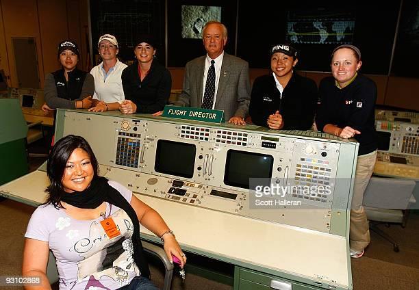 LPGA players Christina Kim Mindy Kim Leah Wigger Brandi Jackson Jane Park and Stacy Lewis pose inside the Apollo control room with former NASA flight...
