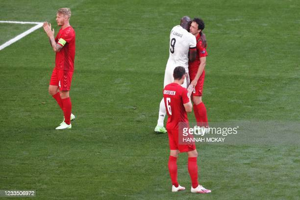 Players clap in support of Denmark's midfielder Christian Eriksen during the UEFA EURO 2020 Group B football match between Denmark and Belgium at the...