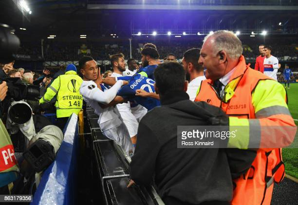 Players clash and fans are restrained after a challenge by Ashley Williams of Everton on Anthony Lopes of Lyon during the UEFA Europa League Group E...