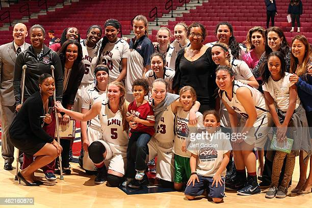 Players, coaches and guests of the Loyola Marymount Lions women's basketball team smile as they pose for a photo with Associate Professor of African...