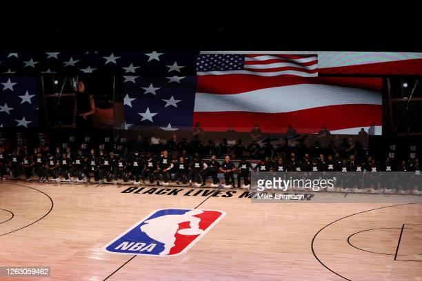 Players, coaches and staff kneel during the national anthem before the game between the Houston Rockets and the Dallas Mavericks at The Arena at ESPN...