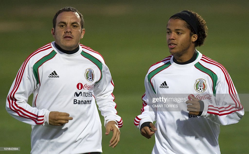Players Cuauhtemoc Blanco (L) and Giovanni Dos Santos, of the Mexican national team, jog during a training session at the Waterstone College in Johannesburg on June 5, 2010. Mexico will kick off the four-yearly tournament next Friday against host South Africa at Soccer City in Johannesburg. AFP PHOTO/Omar TORRES