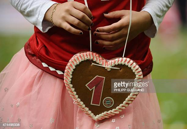 A player's daughter holds a gingerbread heart decorated with Bayern Munich's logo and number 1 as they celebrate winning their 25th Bundesliga title...