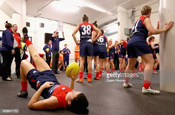 Players do their final stretches before running out onto the field ahead of the women's AFL match between the Melbourne Demons and the Brisbane Lions...