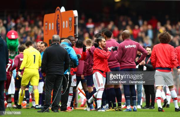 Players don't shake hands ahead of the Premier League match between Arsenal FC and West Ham United at Emirates Stadium on March 07 2020 in London...
