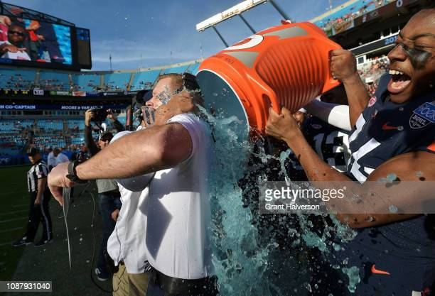Players douse head coach Bronco Mendenhall of the Virginia Cavaliers after a win against the South Carolina Gamecocks during the Belk Bowl at Bank of...
