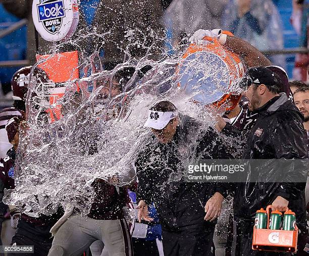 Players douse head coach Dan Mullen of the Mississippi State Bulldogs with water to celebrate a win against the North Carolina State Wolfpack during...