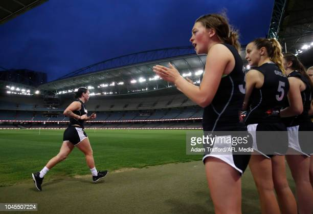 Players encourage Sabreena Duffy as she performs in the 2km time trial during the AFLW Draft Combine at Marvel Stadium on October 3 2018 in Melbourne...