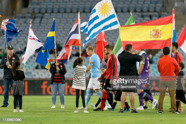 Players enter the pitch amid flags representing multicultural festivities at round 23 of the Hyundai A-League Soccer between Western Sydney Wanderers...