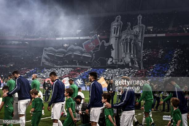Players enter the pitch before the French L1 football match between Olympique Lyonnais and AS SaintEtienne on March 1 2020 at the Groupama stadium in...