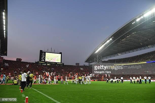 Players enter the pitch prior to the JLeague match between Urawa Red Diamonds and Omiya Ardija at the Saitama Stadium on July 17 2016 in Saitama Japan
