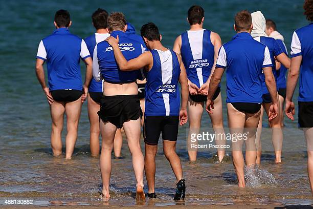 Players enter the water during a North Melbourne Kangaroos AFL recovery session on September 14 2015 in Melbourne Australia