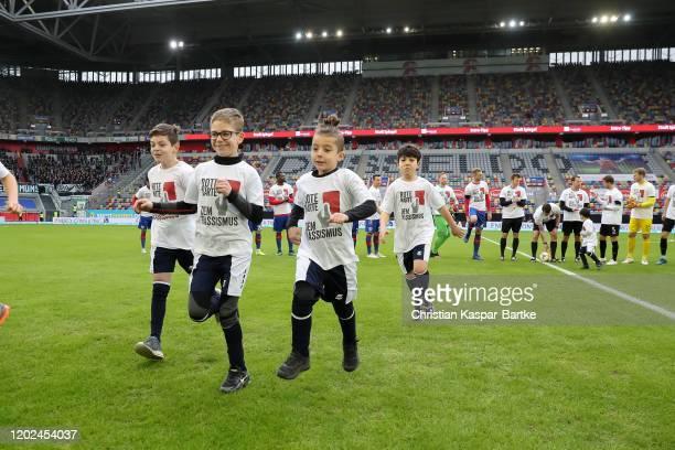 Players escort kids wear a shirt with a print Red card against racism prior to the 3 Liga match between KFC Uerdingen and Preussen Muenster at Merkur...