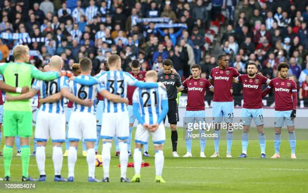 Players fans and officials observe a minutes silence for Remembrance Day prior to the Premier League match between Huddersfield Town and West Ham...